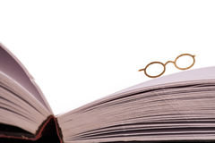 Reading glasses on book edge. Reading glasses resting on the edge of an open blank book with white pages and space for text Stock Photos