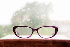 Reading glasses and book on rainy window Royalty Free Stock Photography