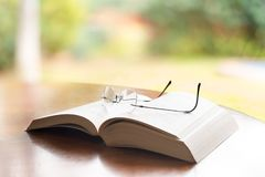 Reading glasses on book. Reading glasses on top of a book royalty free stock photo