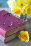 Reading glasses books Flowers. Reading glasses on pink books with daffodil flowers royalty free stock photo