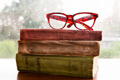 Reading glasses and books on rainy window Royalty Free Stock Image