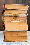 Reading glasses and books on wooden background concept Stock Images