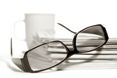 Reading Glasses and Coffee Cup on Magazines Pile stock photos