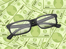 Reading glasses on dollar background Royalty Free Stock Images