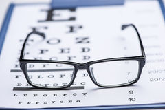 Reading glasses on eye chart. A pair of orange and black spectacles on an eye chart royalty free stock images