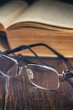 Reading glasses in front of old yellow book. On rustic wooden background stock image