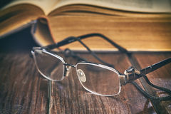 Reading glasses in front of old yellow book. On rustic wooden background royalty free stock photos