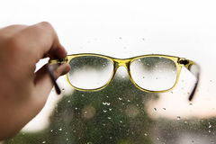 Reading glasses in hand on rainy window background Royalty Free Stock Photography