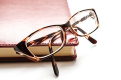 Reading glasses lie on a notebook stock image