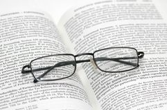 Reading glasses with light fra. Reading glasses  with light frame over the open book Stock Photos
