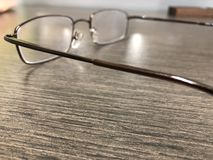 Reading glasses lying on office desk stock photos