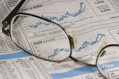 Information about stock prices in newspaper. Reading glasses is on a newspaper with the latest numbers and statistics in the stock market Royalty Free Stock Image