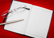 Reading glasses on notepad Stock Photography