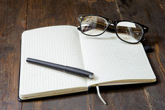 Reading glasses and notepad on wooden background Royalty Free Stock Photography