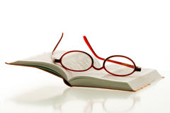Reading glasses on open book Stock Photo