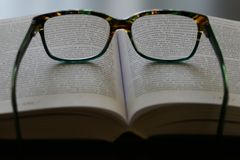 Reading glasses on an open book stock photos