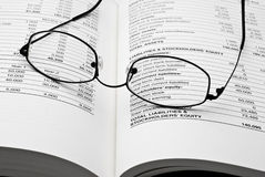Reading glasses on open business book Stock Images