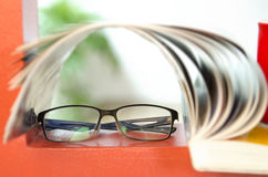 Reading glasses on an orange surface Royalty Free Stock Images