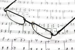 Reading glasses over the music. Sheets Stock Image