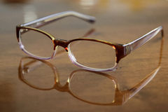 Reading glasses. A pair o reading glasses on a wooden table royalty free stock image