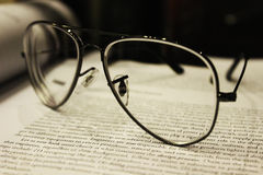 Reading Glasses. A pair of reading glasses sitting on a book denoting education and work Royalty Free Stock Image