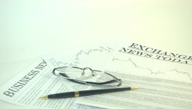 Reading glasses and pen are on the news media stock images