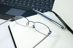 Reading glasses and pen on notebook Stock Photos