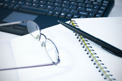 Reading glasses and pen on notebook Stock Photography