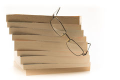 Reading glasses on top of a pile of books. Reading glasses perched on top of a pile of educational books Royalty Free Stock Images
