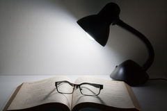 Reading glasses resting on top of open book next to night lamp Stock Photo