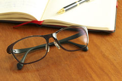 Reading glasses and schedule book and pen Royalty Free Stock Photos