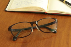 Reading glasses and schedule book and pen Royalty Free Stock Photography