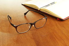 Reading glasses and schedule book and pen Royalty Free Stock Images