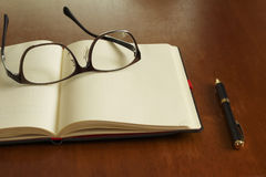 Reading glasses and schedule book and pen Stock Photos