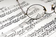 Reading glasses on sheet music. Old reading glasses resting on old sheet music stock photos
