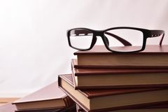 Reading glasses on stack of books with white background. Glasses on stack of books with white background. Concept need glasses to read. Front view. Horizontal stock photos