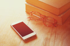 Reading glasses, stack of old books and smart phone over wooden table, retro filtered image Royalty Free Stock Photo