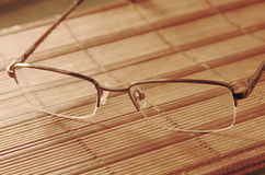 Reading glasses on a table with soft light. Reading glasses on a table with soft light taken closeup stock photo