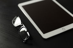 Reading glasses and tablet computer on black desk. Closeup shot of glasses and white tablet Royalty Free Stock Photography