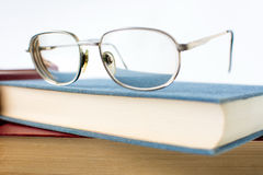 Reading glasses on top of book Stock Images