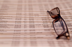 Reading glasses on top of financial paper Stock Images