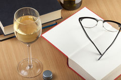Reading glasses and wine glass with some books. Reading glasses and a glass of wine with some books of a wooden table stock photos