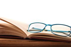 Reading glasses on wood table with open book front. Reading glasses on wood table with open book. Concept need glasses to read. Front view. Horizontal royalty free stock image