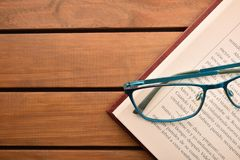 Reading glasses on wood table with open book top. Concept need glasses to read. Top view. Horizontal composition royalty free stock images