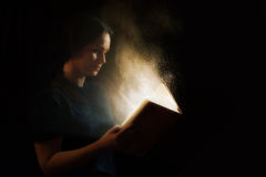 Reading a glowing book Royalty Free Stock Image