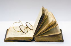 Reading is good. A old open book with a pair of antique glasses on it Royalty Free Stock Photo