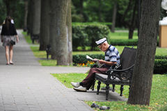 The reading grandfather. The elderly man reads the book in rest park Stock Photography