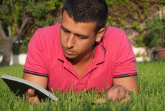 Reading in the grass. A young man is reading a book laying in the grass and enjoying the sun Stock Photo