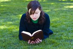 Reading on the grass stock image