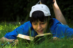 Reading in the grass. Boy reading in the park on a sunny day Stock Photography